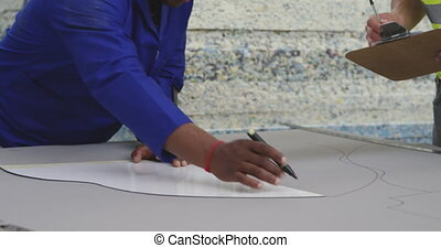 Worker drawing a pattern on a cardboard - Front view close ...