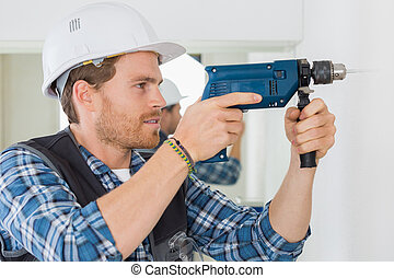 worker drilling a hole on the wall