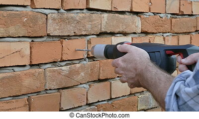 Worker drilling hole in a brick wall - Drilling hole in a...