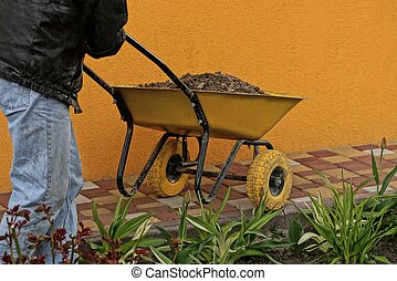 worker driving a yellow wheelbarrow with sand on the sidewalk near the wall in the garden