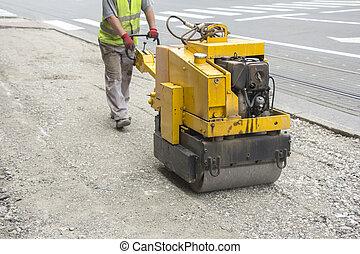 Vibration roller compactor - Worker driving Vibration roller...
