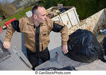 Worker dumping rubbish bags