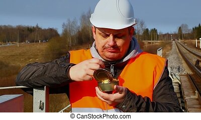 Worker eats canned meat on a railway