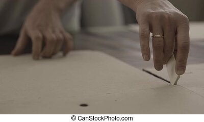 Worker encircle cardboard by a piece of chalk in furniture factory