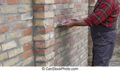 Worker examining brick wall - Worker control brick wall with...