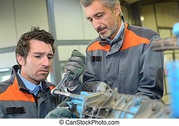 worker fixing a heavy metal part