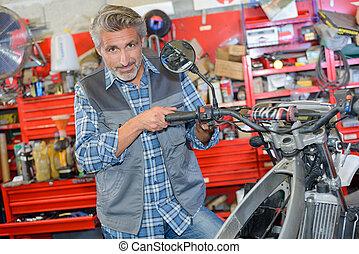 worker fixing a motorbike