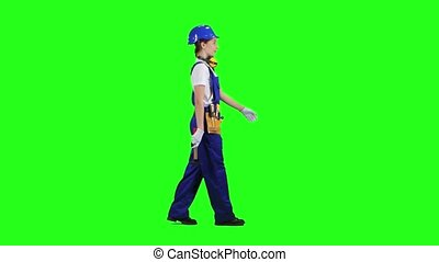 Worker girl comes with a hammer in her hands and in a helmet. Green screen. Side view