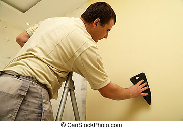 Worker glues new wallpaper