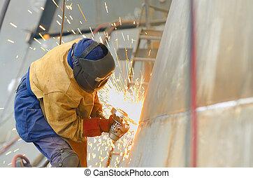 worker grinding metal inside of shipyard