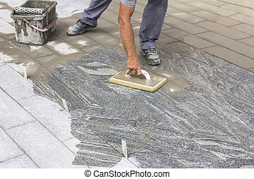 Worker grouting tiles with rubber trowel and gray cement ...
