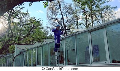 worker guy in uniform washing glass house with high pressure.