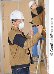 worker hammering chisel on wall at construction site