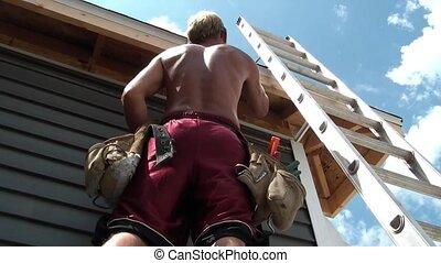 Worker Hammering in Siding - Construction worker hammering...