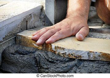 worker hand closeup lying flagstone on concrete