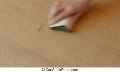 Worker hand sanding wooden plank - Closeup of worker hand...