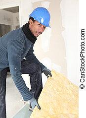 Worker handling insulation