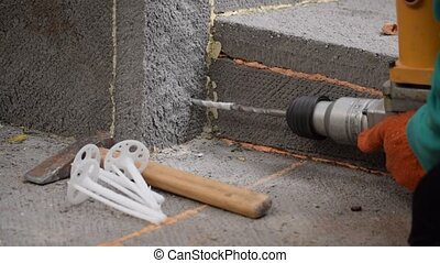 Worker hands drilling a hole on house foundation with...