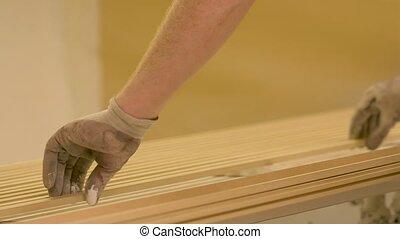 worker hands placing fibreboard planks at workshop -...