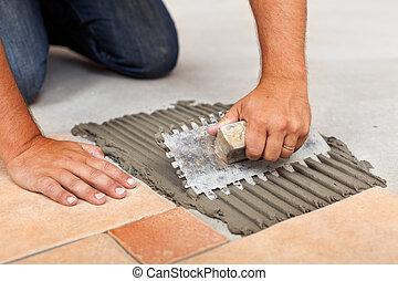 Worker hands spreading adhesive for ceramic floor tiles - closeup