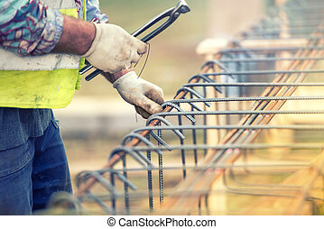 worker hands using steel wire and pliers to secure bars on construction site and preparing for concrete pouring
