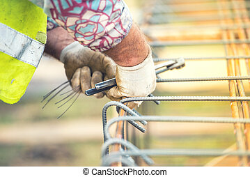 worker hands using steel wire and pincers to secure steel bars, preparing for concrete pouring on construction site