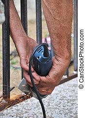Hands of metal worker with grinder producing