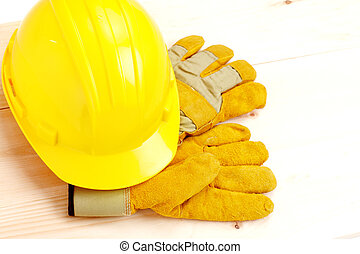 Worker hard hat and gloves over wood plank.