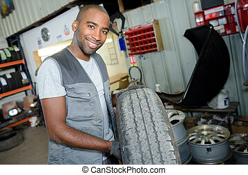 worker holding a tire