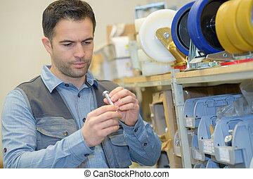 worker holding metal bolt