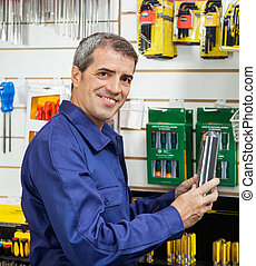 Worker Holding Packed Product In Hardware Store