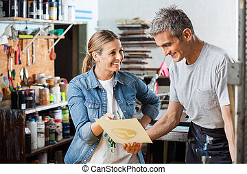Worker Holding Paper While Colleague Smiling At Him