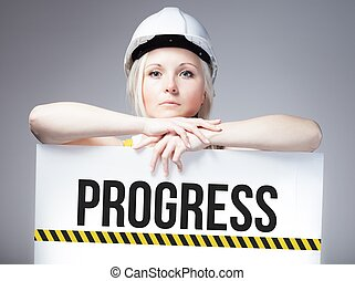 Worker holding progress sign on information board