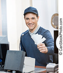 Worker Holding Tickets At Box Office Counter - Portrait of...