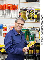 Worker Holding Tool Package In Hardware Shop