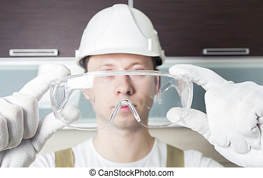 Worker holding transparent safety glasses
