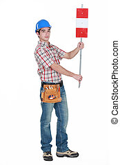 Worker holding up road sign