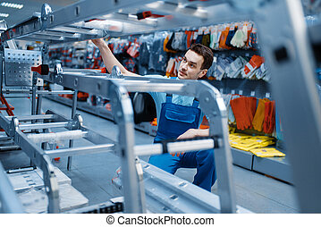 Worker holds aluminum stepladders in tool store