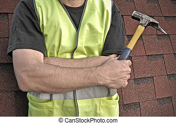 hammer in hands on background of roof shingles