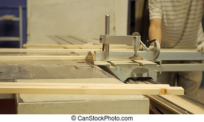 Worker in a carpentry workshop sawing boards on a machine