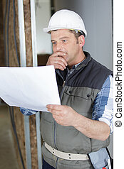 worker in a hard hat looking at plan