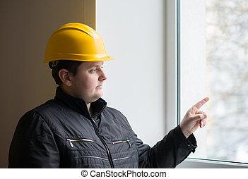 Worker in a helmet on a background window