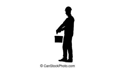 Worker in a helmet paints a building with a roller. Silhouette. White background