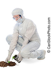 Worker in a protective suit examines the ground on a white background