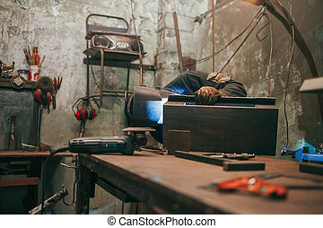 Worker in a welder mask works in a workshop for welding iron. Man makes iron products. Guy works with a welding machine using a mask to protect his eyes from dangerous rays