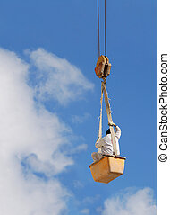 Worker in air - A worker hanging on a steel cable.