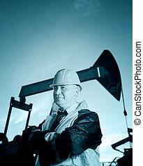 Worker in an Oil field - Oil worker in uniform and helmet on...