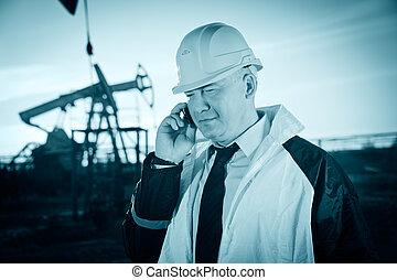 Worker in an Oil field - Oil worker in uniform and helmet,...