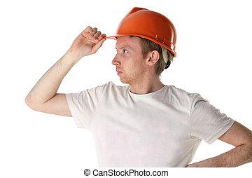 Worker in an orange helmet looks into the distance