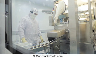 Worker in apron, cap, gloves with tablet checking process at production line in factory. Quality Control Workers Examining Pills in Lab. Pharmaceutical lab technicians inspecting the quality of medical pills